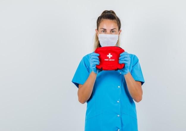 Vrouwelijke arts in blauw uniform, masker, handschoenen die ehbo-doos houden en voorzichtig kijken