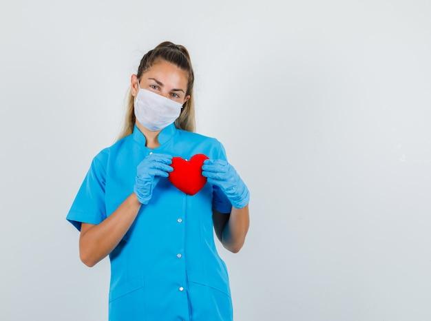 Vrouwelijke arts in blauw uniform, masker, handschoenen die rood hart houden en optimistisch kijken