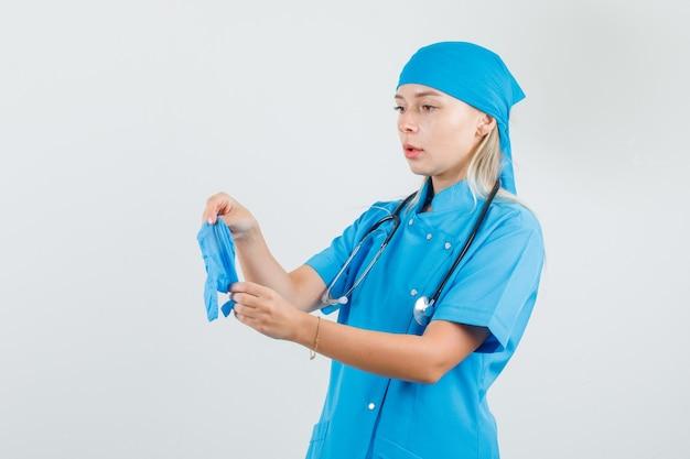 Vrouwelijke arts in blauw uniform medische handschoenen te houden en voorzichtig te kijken