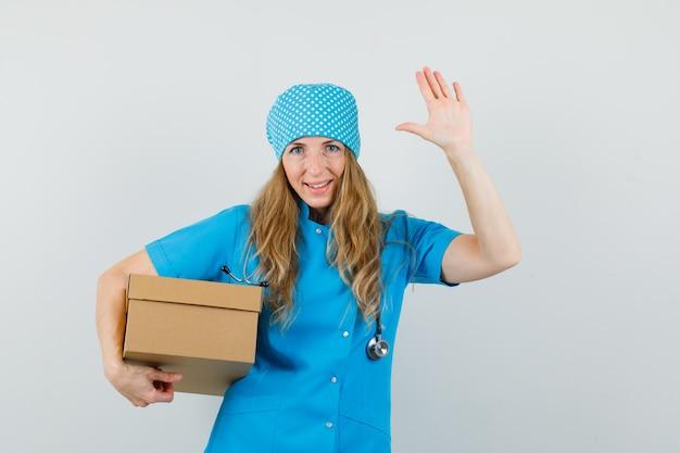 Vrouwelijke arts in blauw uniform met kartonnen doos, zwaaiende hand en op zoek vrolijk