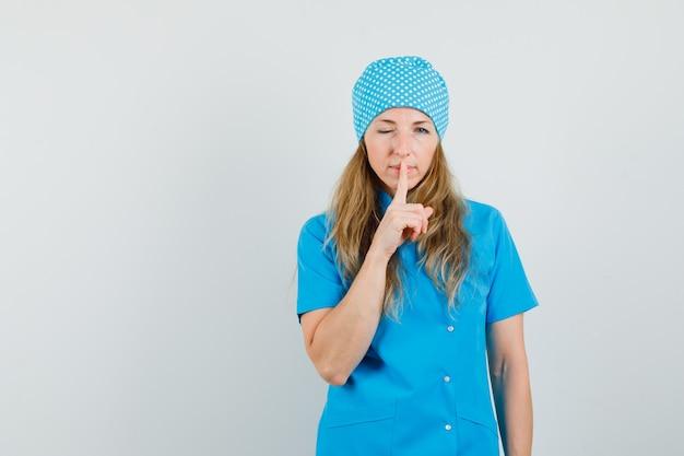 Vrouwelijke arts in blauw uniform met stilte gebaar en knipogend oog