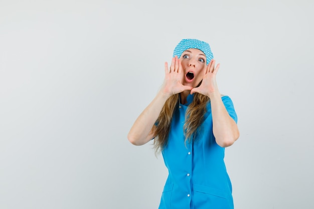 Vrouwelijke arts in blauw uniform schreeuwen met handen in de buurt van mond