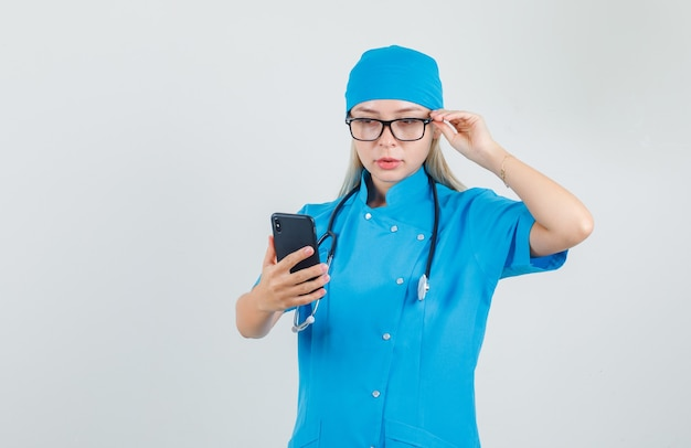 Vrouwelijke arts in blauw uniform smartphone met hand op glazen te houden en bezig te kijken