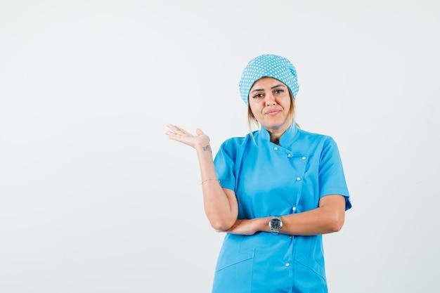 Vrouwelijke arts in blauw uniform spreidt opgeheven handpalm opzij en kijkt verward