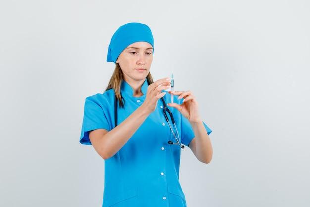 Vrouwelijke arts in blauw uniform spuit voor injectie te houden en bezig te kijken