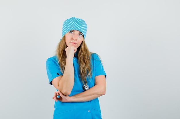 Vrouwelijke arts in blauw uniform staande in denken pose en hoopvol op zoek