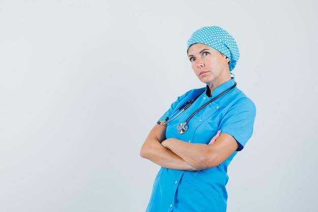 Vrouwelijke arts in blauw uniform staande met gekruiste armen en peinzend, vooraanzicht op zoek.