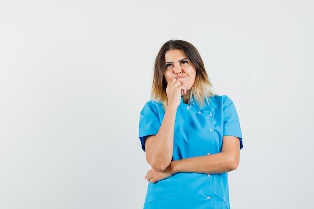 Vrouwelijke arts in blauw uniform staat in denkende houding en kijkt besluiteloos