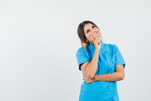 Vrouwelijke arts in blauw uniform staat in denkende houding en kijkt besluiteloos?