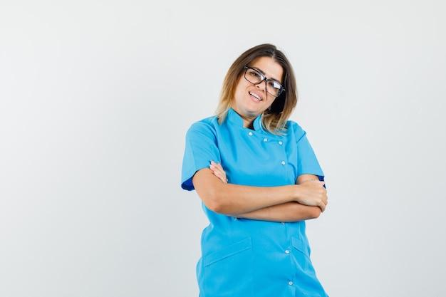 Vrouwelijke arts in blauw uniform staat met gekruiste armen en ziet er vrolijk uit