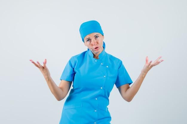 Vrouwelijke arts in blauw uniform verhogen handen op vragende manier en op zoek in verwarring, vooraanzicht.