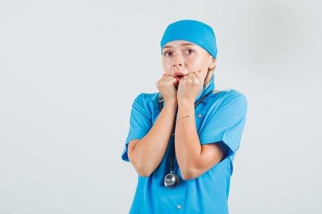 Vrouwelijke arts in blauw uniform vuisten in de buurt van mond houden en bang kijken
