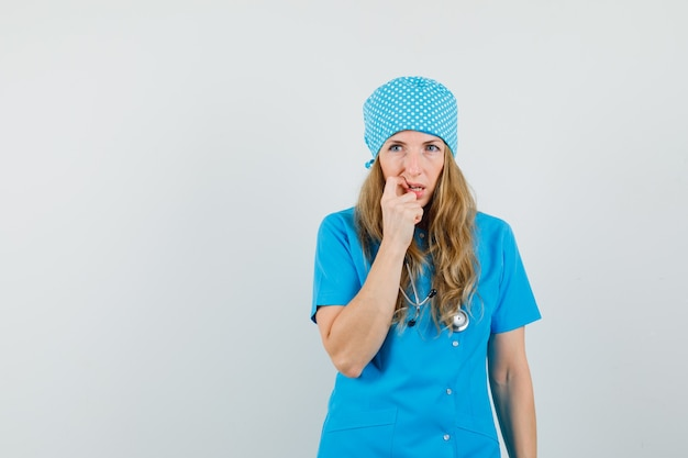 Vrouwelijke arts in blauw uniform wegkijken terwijl denken en hulpeloos kijken