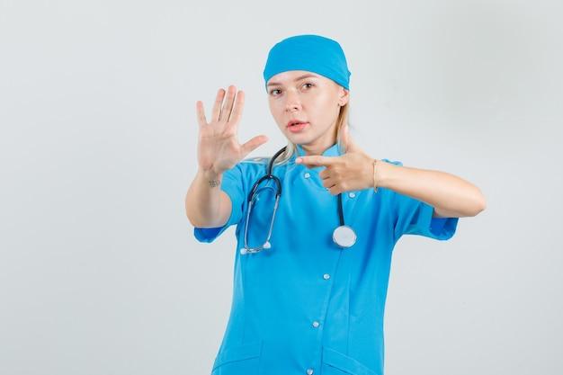Vrouwelijke arts in blauw uniform wijzend op opgeheven handpalm en kijkt serieus