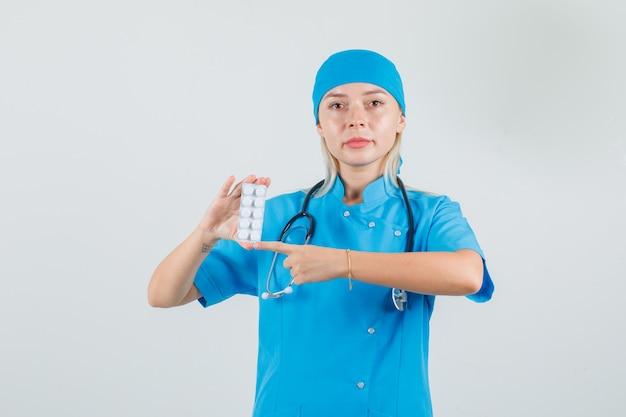 Vrouwelijke arts in blauw uniform wijzend op pakje pillen en op zoek ernstig