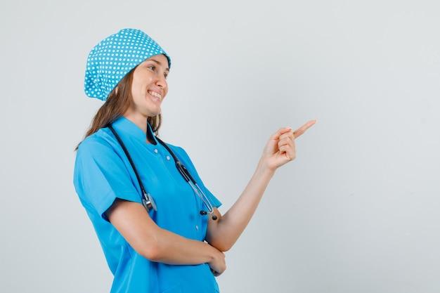 Vrouwelijke arts in blauw uniform wijzende vinger naar kant en kijkt blij