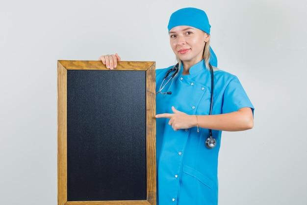 Vrouwelijke arts in blauw uniform wijzende vinger op bord en op zoek positief