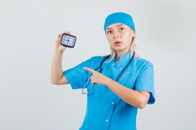 Vrouwelijke arts in blauw uniform wijzende vinger op klok en voorzichtig kijken