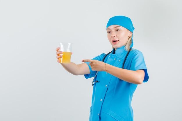 Vrouwelijke arts in blauw uniform wijzende vinger op vruchtensap