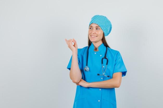 Vrouwelijke arts in blauw uniform wijzende vinger weg en op zoek blij