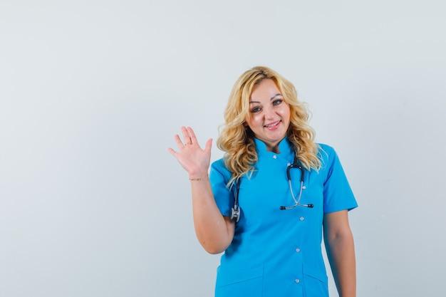 Vrouwelijke arts in blauw uniform zwaaiende hand voor afscheid en op zoek naar tevreden ruimte voor tekst