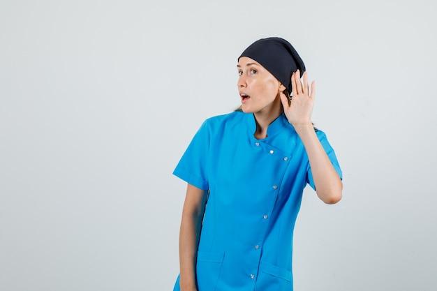 Vrouwelijke arts in blauw uniform, zwarte hoed die hand achter oor houdt om te luisteren en gericht te kijken