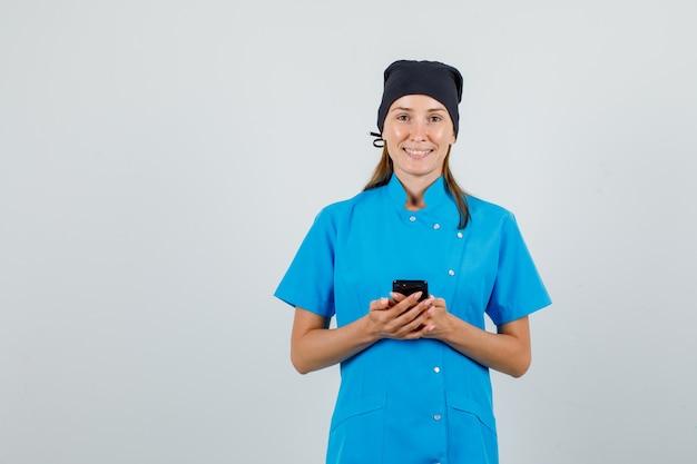 Vrouwelijke arts in blauw uniform, zwarte hoed smartphone houden en vrolijk kijken