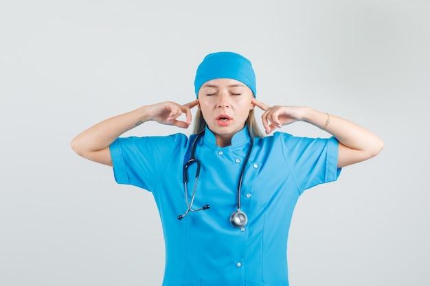 Vrouwelijke arts in blauwe uniforme oren met vingers inpluggen en geërgerd op zoek