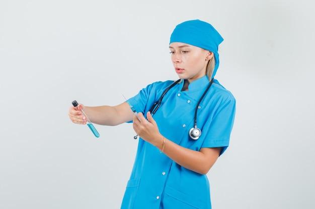 Vrouwelijke arts in blauwe uniforme reageerbuis en spuit te houden