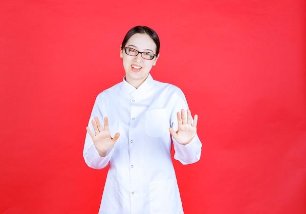 Vrouwelijke arts in brillen die op rode achtergrond staan en iets stoppen.
