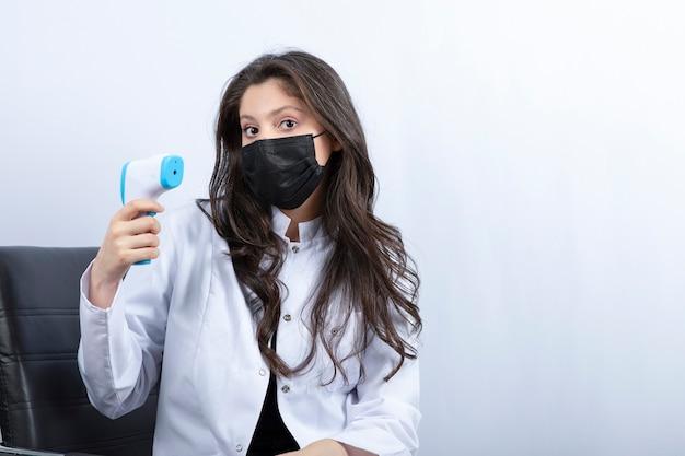 Vrouwelijke arts in de medische thermometer van de maskerholding en het bekijken voorzijde.