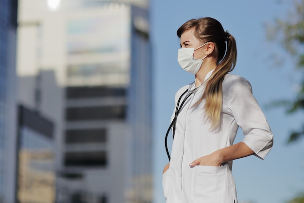 Vrouwelijke arts in een beschermend masker tegen de achtergrond van gebouwen met meerdere verdiepingen van de stad