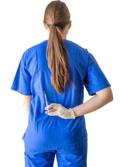 Vrouwelijke arts in een blauw medisch uniform met gesteriliseerde handschoenen die een spuit achter haar tegenhouden