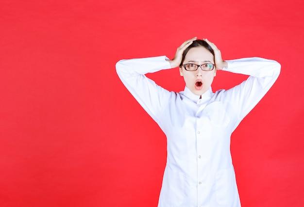 Vrouwelijke arts in een bril die op een rode achtergrond staat en het hoofd met handen vasthoudt en ziet er doodsbang uit.