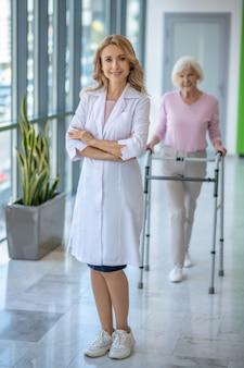 Vrouwelijke arts in een laboratoriumjas die zich met gekruiste wapens bevindt en glimlacht terwijl haar patiënt naar haar komt
