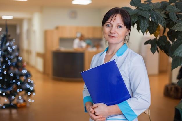 Vrouwelijke arts in een medische jurk houdt een blauwe map voor documenten vast in de ziekenzaal van de kerstboom.