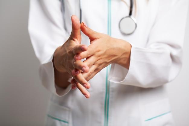 Vrouwelijke arts in een witte jas desinfecteert haar handen met antisepticum