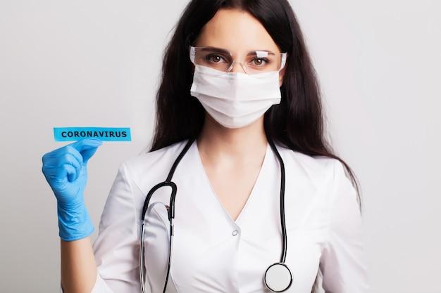 Vrouwelijke arts in een witte jas en masker met de inscriptie coronavirus