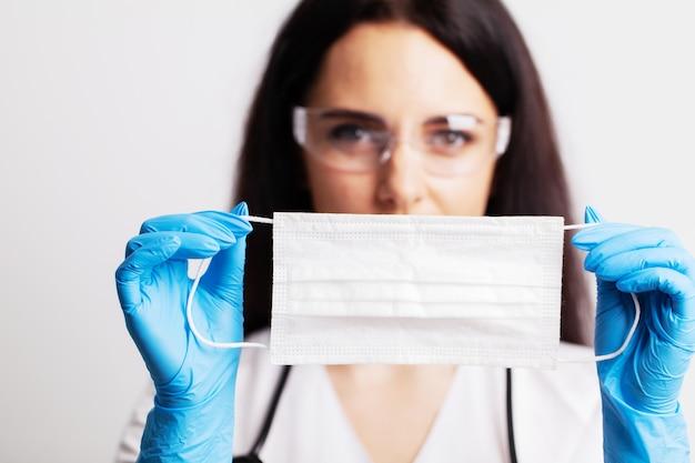 Vrouwelijke arts in een witte jas met een chirurgisch masker