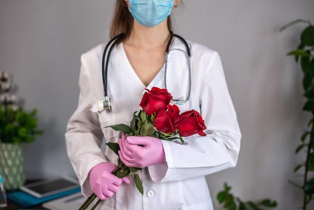 Vrouwelijke arts in een witte jurk en roze handschoenen en met een stethoscoop