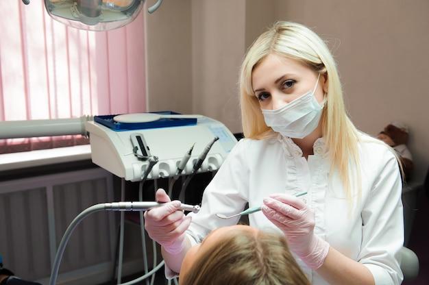 Vrouwelijke arts in eenvormig de tanden van de vrouwelijke patiënt controleren