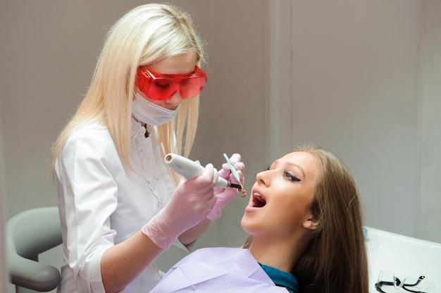 Vrouwelijke arts in eenvormig die de tanden van de vrouwelijke patiënt in tandkliniek controleren.