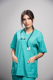 Vrouwelijke arts in eenvormige status op grijs