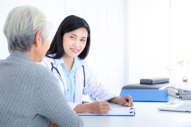 Vrouwelijke arts in gesprek met oudere patiënten in het ziekenhuis. oudere patiëntenzorg en gezondheidszorg, medisch concept.