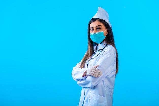 Vrouwelijke arts in masker doet zich voor als een professional.