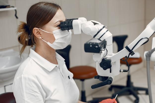 Vrouwelijke arts in medisch masker. dokter voert een onderzoek uit. de vrouw voert een microbiologisch onderzoek uit
