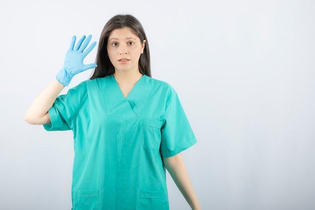 Vrouwelijke arts in medische handschoenen die handen op wit tonen.