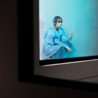Vrouwelijke arts in pandemische apparatuur zittend in het ziekenhuis moe