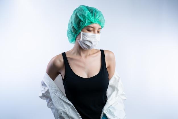 Vrouwelijke arts in ppe (persoonlijke beschermingsmiddelen), verwijder de hazmat-suite.