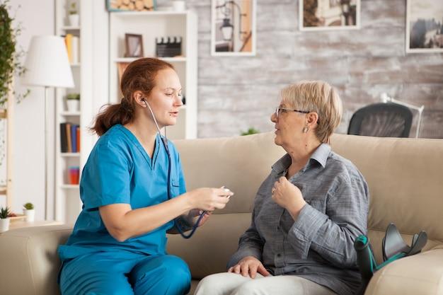 Vrouwelijke arts in verpleeghuis die stethoscoop gebruikt om oud vrouwenhart te luisteren.
